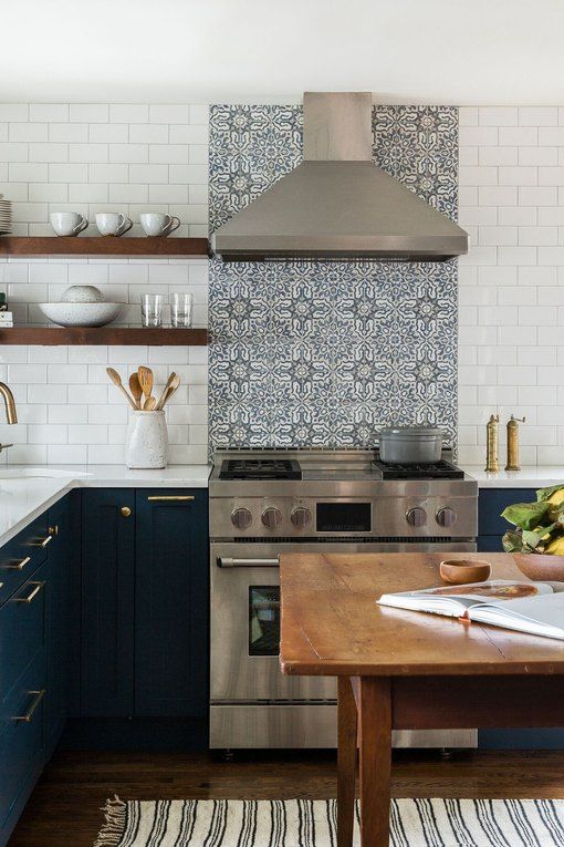 a navy L-shaped kitchen with a white and patterned tile backsplash and a wooden table as a kitchen island or for having meals