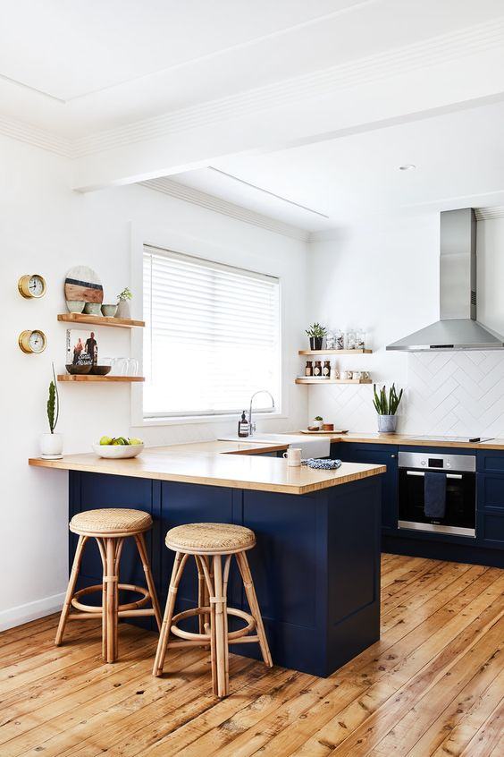 a navy U-shaped kitchen with light-stained butcherblock countertops, a white tile backsplash and rattan stools