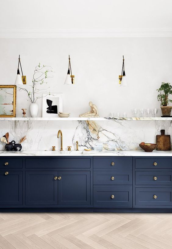 a navy one wall kitchen with a white stone backsplash and countertops, a stone shelf and sconces is super chic