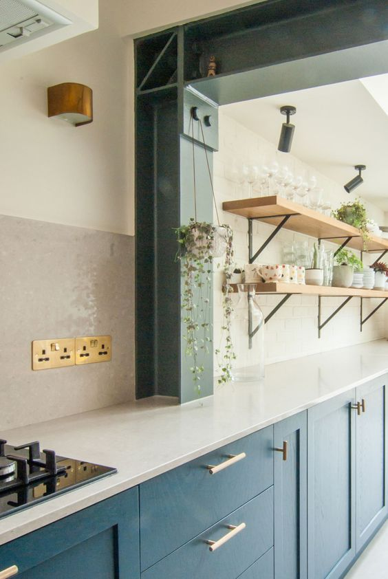 a navy one wall kitchen with a white subway tile backsplash and countertops, open blonde wood shelves and greenery