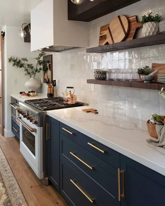 a navy shaker style kitchen with a white square tile backsplash and white quartz countertops plus brass touches and floating shelves