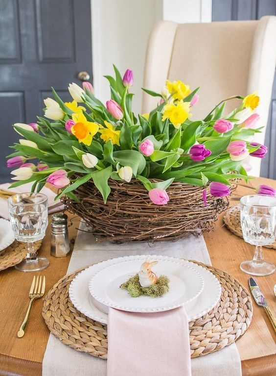 a nest with colorful tulips and daffodils is a bright and fun spring centerpiece that is cool for Easter too
