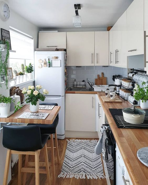 a neutral L shaped kitchen with grey tiles, butcherblock countertops and potted greenery and blooms