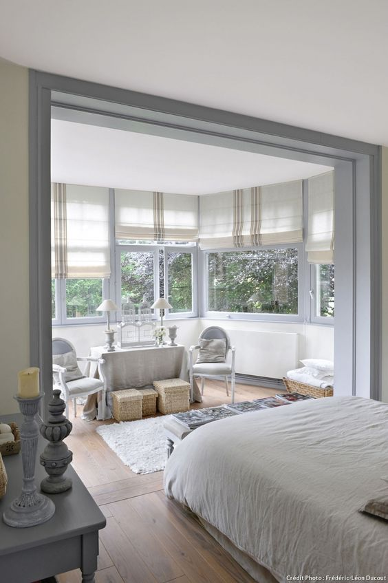 a neutral farmhouse bedroom with a large bow window and a seating nook placed there, the sleeping zone seems separated