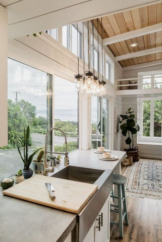a neutral farmhouse kitchen done with beadboard, a glazed wall and additional clerestory windows plus potted plants