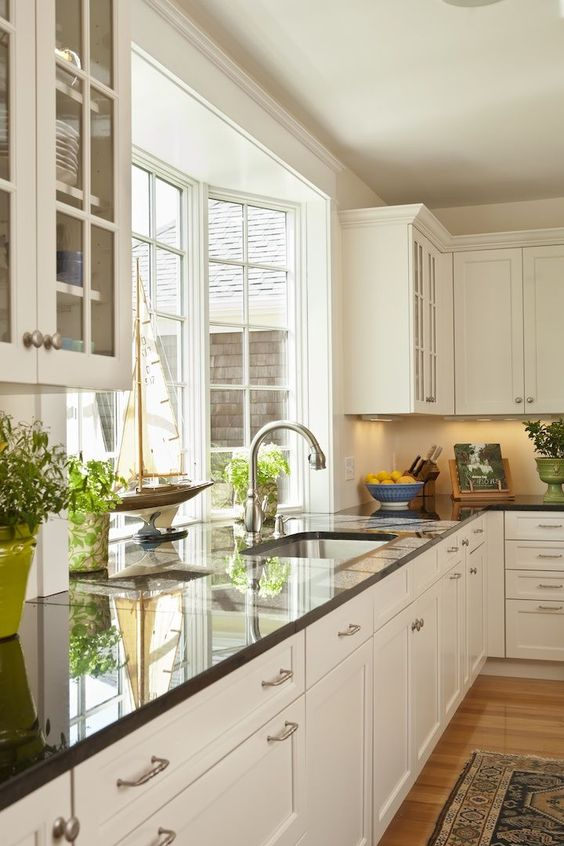 a neutral farmhouse kitchen with black countertops and a pretty bow window that fills the space with natural light