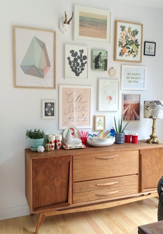 a pastel gallery wall with white and blonde wood frames and pastel artworks and prints is a chic and delicate idea