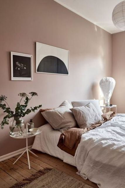 a pretty Scandinavian bedroom with mauve walls, a comfy bed and neutral bbedding, mismatching nightstands and cool artworks