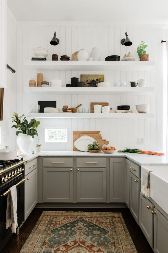 a pretty U-shaped kitchen with grey shaker style cabinets, white countertops, white floating shelves and brass and gold touches for elegance