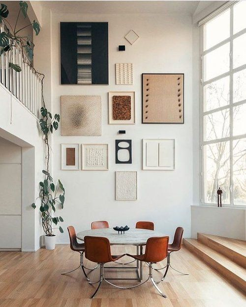 a pretty abstract gallery wall in neutrals, white and black, with various textures is a stylish idea to try