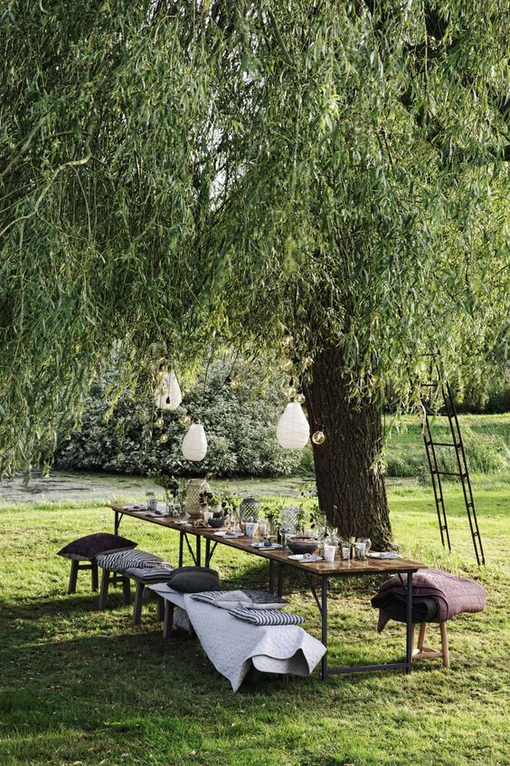 a pretty and cool garden dining zone under the tree, with a long table, benches and a stool, pillows and blankets, pendant lamps
