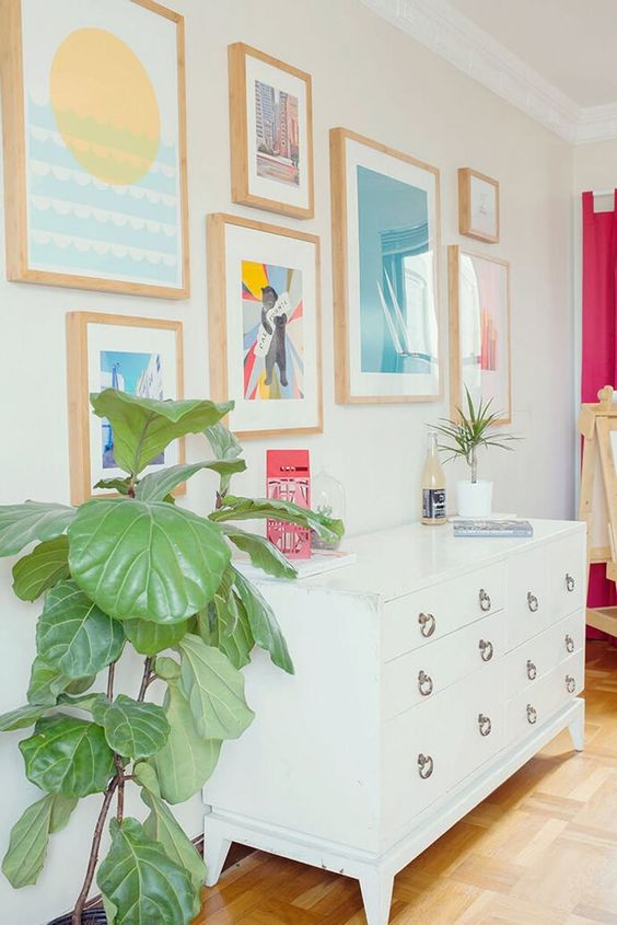 a pretty colorful gallery wall with matching light stained frames and bold and pastel shades is amazing