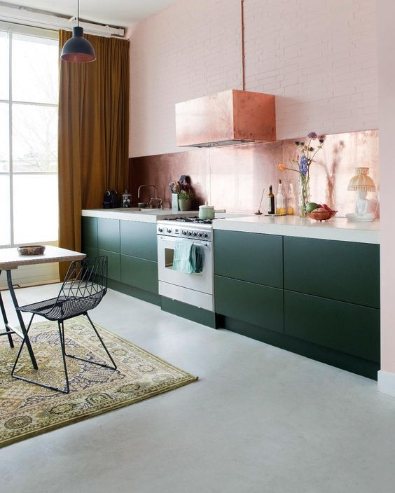a pretty dark green one wall kitchen with a white stone countertop, a rose gold backsplash and a matching hood
