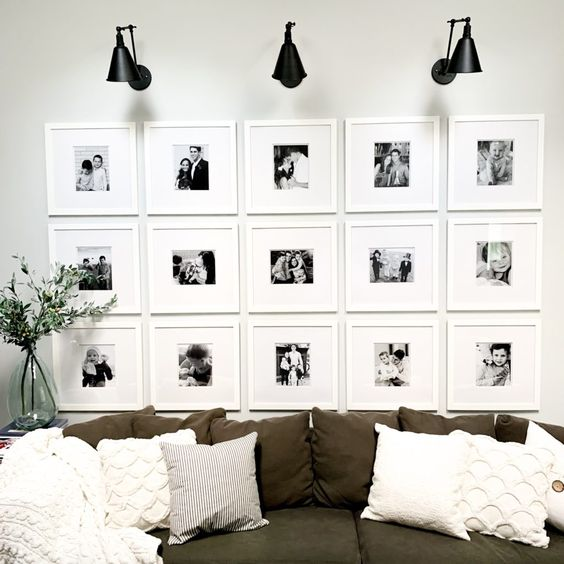a pretty gallery wall with white frame sand matting and small black and white family pics accented with sconces
