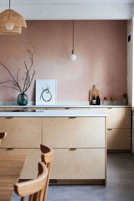 a pretty kitchen with a mauve accent wall, plywood cabinets, white countertops and pendant lamps