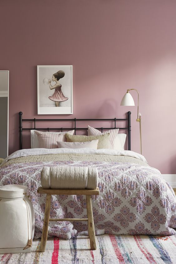 a pretty mauve bedroom with a black forged bed, neutral and pastel bedding, a stool, a sconce and a cool artwork