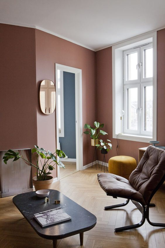 a pretty mauve living room with chic and refined furniture, potted greenery and a chic mirror is a very stylish space