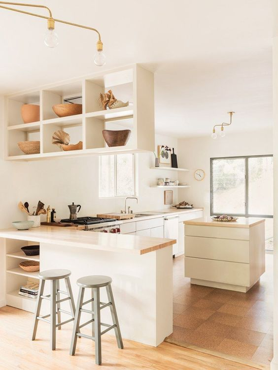 a pretty modern and neutral L-shaped kitchen with a suspended shelf, small kitchen island and butcherblock coutnertops