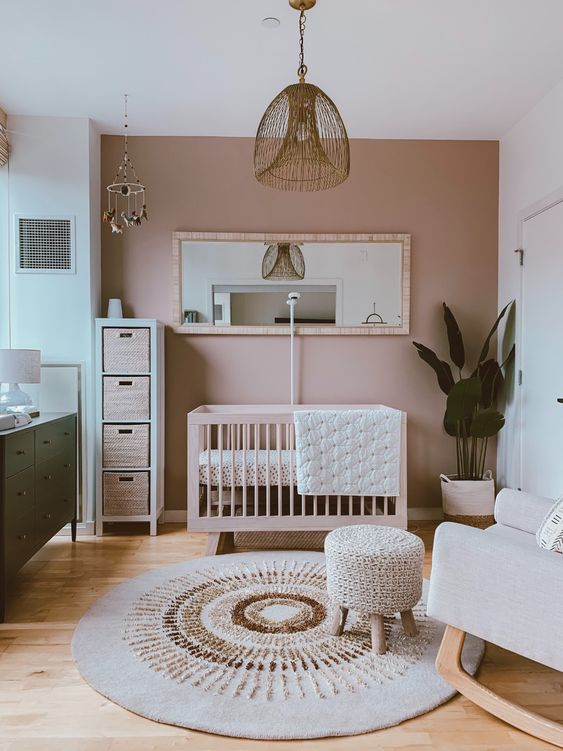 a pretty nursery with a mauve accent wall, stylish mid-century modern furniture, pendant lamps and a statement plant