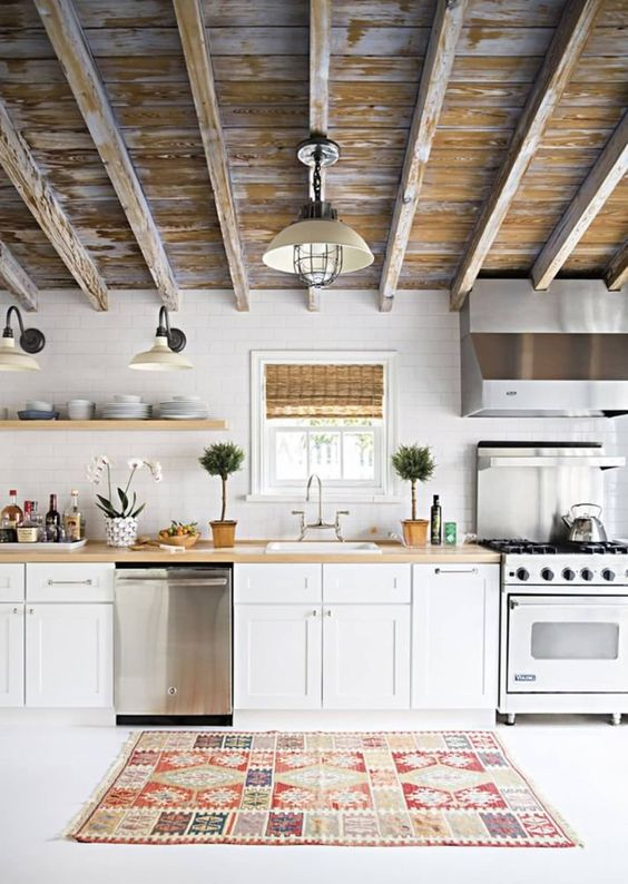 a pretty one wall kitchen with white cabinets, butcherblock countertops and a shabby chic ceiling is very welcoming