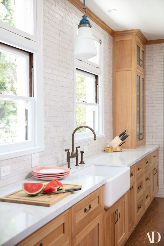 a pretty stained kitchen with white butcherblock countertops, a white subway tile backsplash and lovely retro pendant lamps