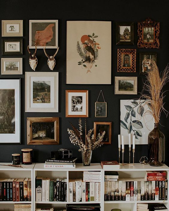 a refined and chic gallery wall with mismatching frames, artworks and antlers is a pretty idea with a vintage feel