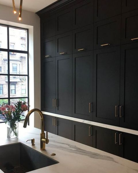 a refined black shaker style kitchen with white quartz countertops, brass and gold touches is a very stylish and elegant space