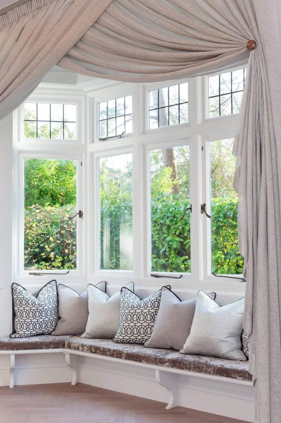 a refined bow window nook with a windowsill seating space with pillows and exquisite neutral curtains