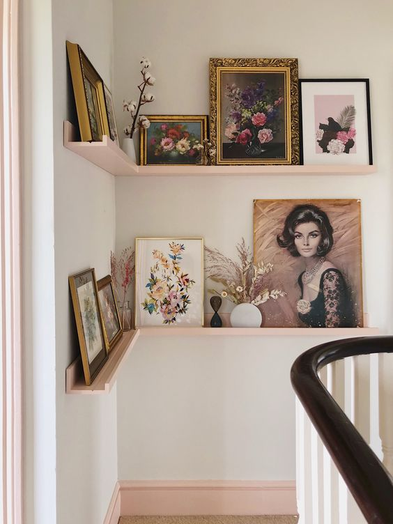 a refined gallery wall done with blush corner ledges, vintage artworks in gold and black frames, dried leaves and blooms in vases