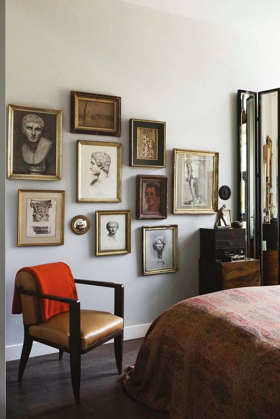 a refined gallery wall with gilded frames and vintage portraits and statue heads is a chic idea for a vintage space