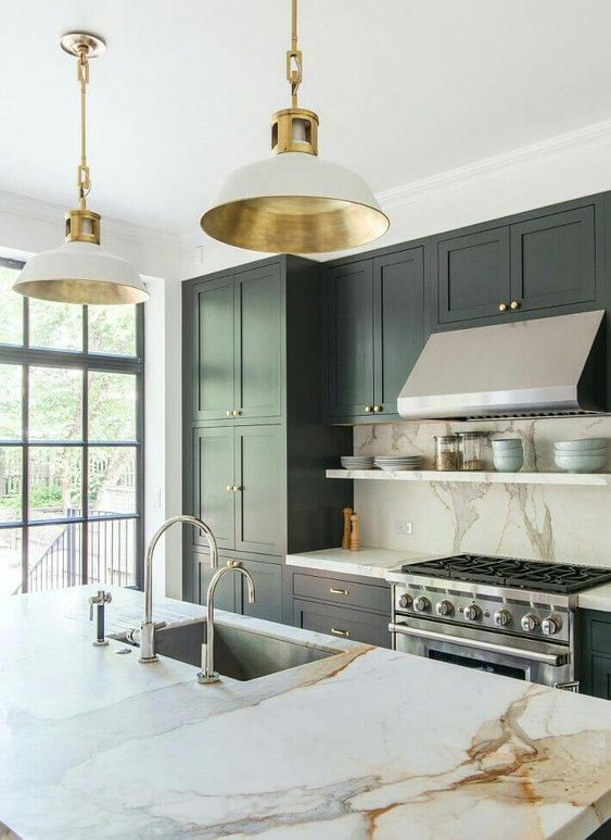 a refined hunter green kitchen with white marble countertops and a backsplash, elegant white and gold lamps and stainless steel appliances