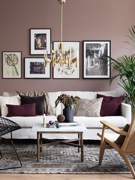 a refined living room with mauve walls, a creamy sofa, a bright gallery wall and mismatching chairs