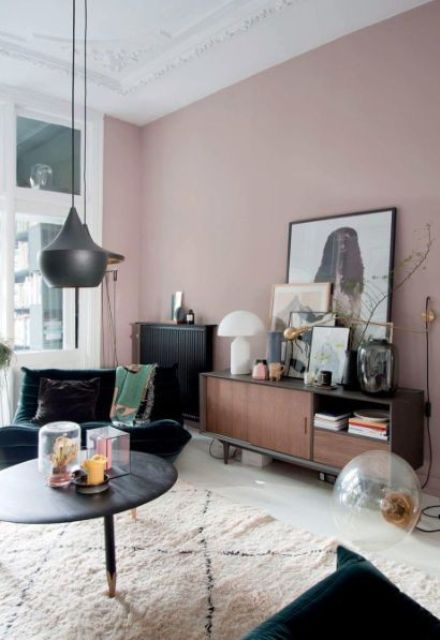 a refined mauve living room with dark furniture, some artworks, pretty dark and gold lamps is chic