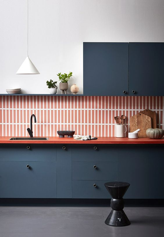 a refined navy one wall kitchen with an orange skinny tile backsplash plus an orange countertop and a white pendant lamp