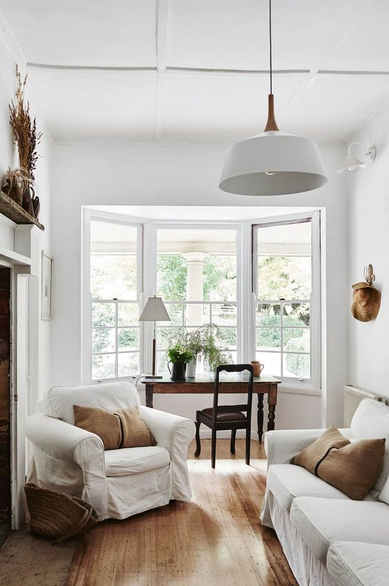 a refined neutral living room with white furniture, rust-colored pillows,a  vintage desk and chair by the bow window