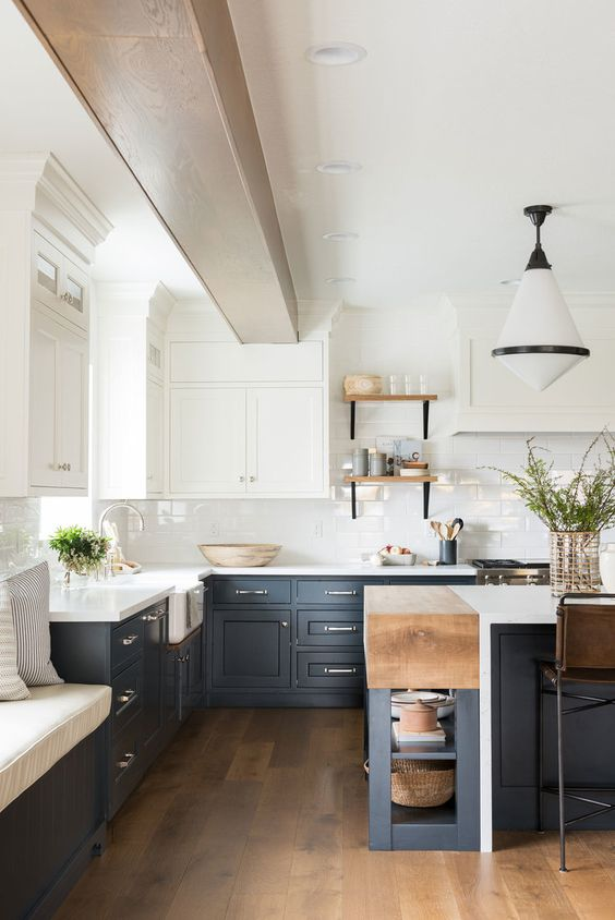 a refined two tone kitchen with navy and white shaker style cabinets, white countertops and a subway tile backsplash plus a retro pendant lamp