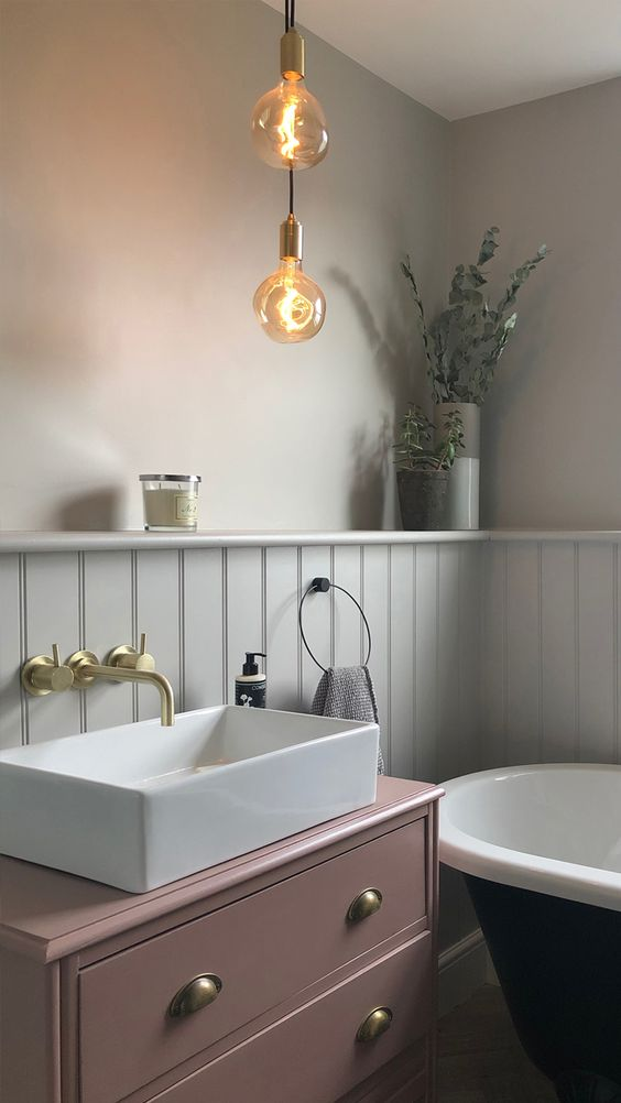 a refined vintage-inspired bathroom with a mauve vanity, black and white appliances and hanging bulbs
