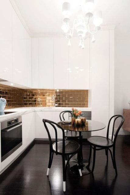a refined white L shaped kitchen with a shiny copper tile backsplash, vintage chairs and a white chandelier wows