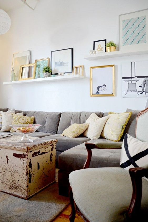 a relaxed gallery wall with two ledges, bold and black and white art, empty frames, bottles, vases, potted plants