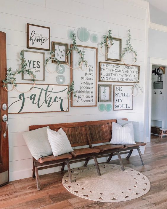 a rustic free form gallery wall with stained wood frames, various signs and prints and lots of embroidery hoops with greenery