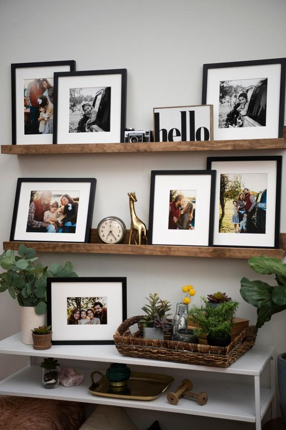 a rustic gallery wall with colorful and black and white artworks in black frames, a clock, a camera and a statuette plus some greenery