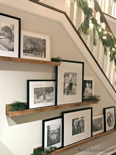 a rustic gallery wall with stained wooden ledges attached to the staircase, black and white artworks and greenery is cool