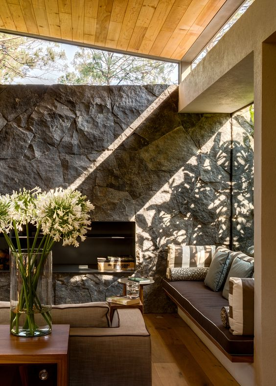 a rustic living room with a stone accent wall, chic furniture, a large window and some clerestory ones for more light