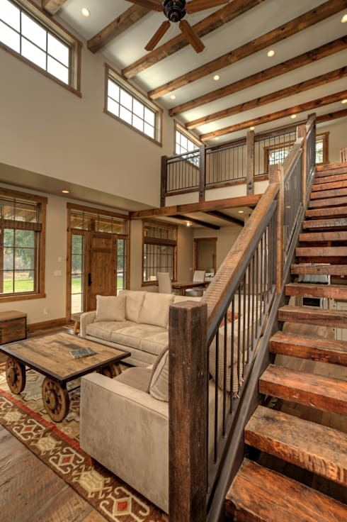 a rustic living room with wooden beams on the ceiling and built-in lights, clerestory windows, neutral furniture and a coffee table on casters