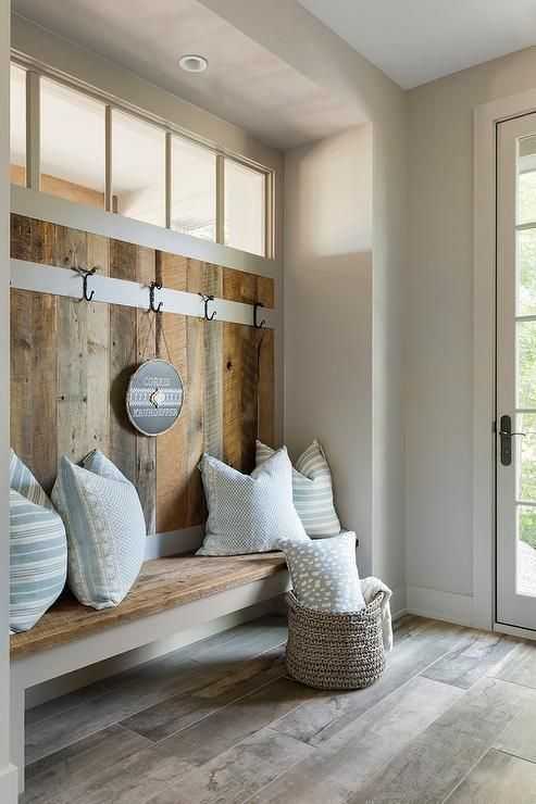 a rustic mudroom with a glass door and a clerestory window for additional light inside is a cozy space