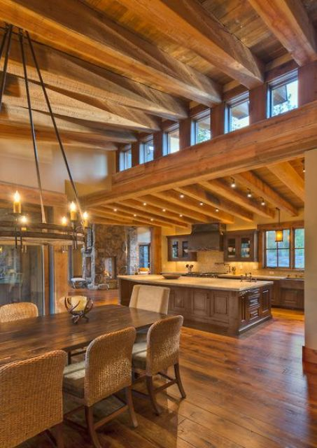 a rustic space with a slanted wooden ceiling with beams, heavy wooden furniture and lights plus clerestory windows for more light inside
