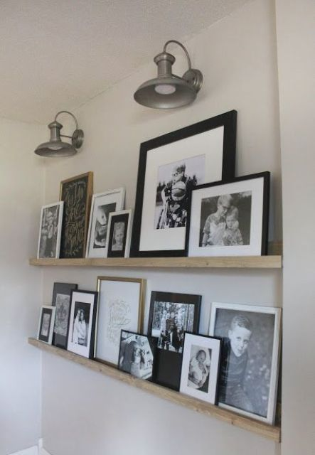 a rustic vintage gallery wall with light stained wooden ledges, family pics in mismatching frames and vintage wall sconces over them