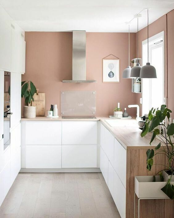 a serene kitchen with mauve walls, white minimalist cabinetry, wooden countertops, pendant lamps