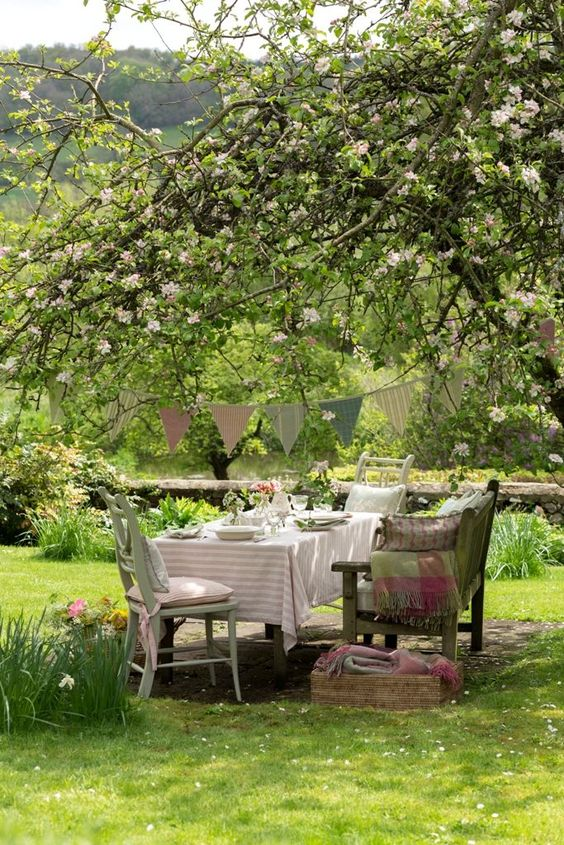a shabby chic dining area under a blooming tree, with a table, chairs and a bench plus pastel textiles