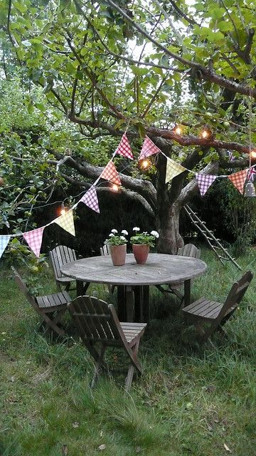a simple rustic dining zone with a round wooden table and wooden chairs, bright garlands over the space and lights